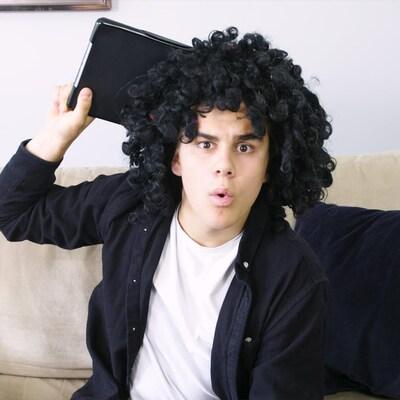 Il porte une perruque frisée et tient une tablette. Il est déguisé en maman.