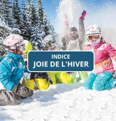 Des enfants s'amusent dans la neige dans une station de ski. Sur l'image, il y a l'indice du concours soit : joie de l'hiver.