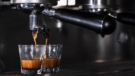 Cafetière espresso versant du café dans deux deux tasses.