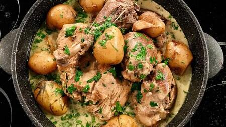 Un chaudron en fonte contenant des morceaux de dinde, des pommes de terre et de la sauce