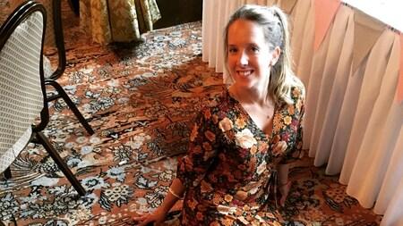 Elle porte une robe fleurie et est assise sur un tapis fleuri.