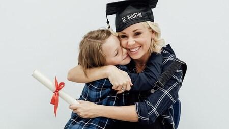 Mariloup Wolfe, un chapeau de diplômé sur la tête, tient son enfant dans ses bras