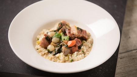 Du riz pilaf dans le fond d'une assiette creuse avec une blanquette de veau et la sauce par dessus.