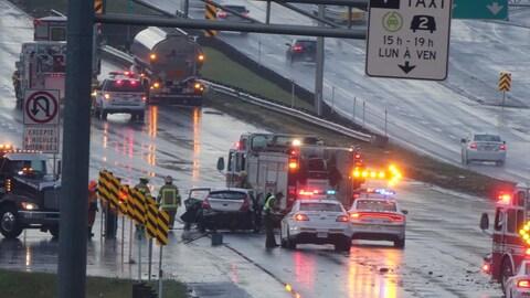 Des agents de la Sûreté du Québec et des pompiers interviennent sur l'autoroute 15 après un carambolage.