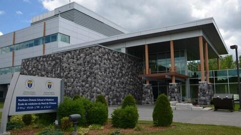 L'entrée d'un bâtiment en pierre et en verre est bordée de petits sapins.