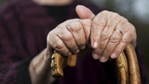 Un aîné tient une canne.