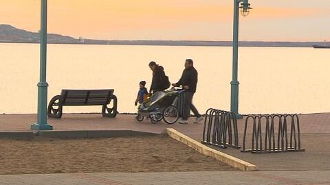 Un couple avec ses deux enfants se promènent au bord de la baie de Sept-Îles au coucher du jour