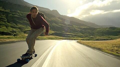 Ben Stiller roule sur une planche à roulettes sur une route déserte entre des collines verdoyantes.