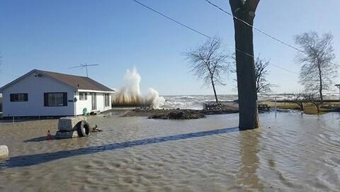 Une maison sur les rives d'un lac. Le terrain est inondé.