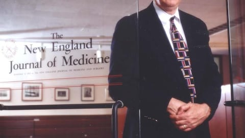 Un homme qui pose devant un bureau du New England Journal of Medicine