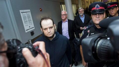 Joshua Boyle est escorté par la police après son allocution aux médias à l'aéroport Pearson de Toronto le 13 octobre 2017.