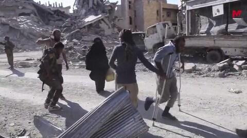 Des civils syriens prenaient la fuite, le 13 octobre 2017, de secteurs encore contrôlés par le groupe armé État islamique à Raqqa.