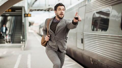 Un jeune homme courre en tentant d'attraper le train de banlieue.