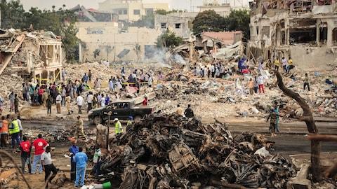 De nombreuses personnes sont photographiées de loin pendant qu'elles se trouvent parmi des débris de maisons et de voitures calcinées. Les immeubles sont pour la plupart détruits.