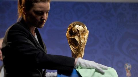 Une préposée nettoie le trophée de la Coupe du monde de la FIFA.