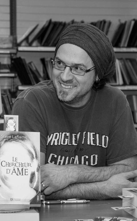 L'écrivain Steve Laflamme lors d'une séance de signature pour son premier roman Le chercheur d'âme. l'auteur est assis derrière une table, souriant. Sur la table on voit son livre.