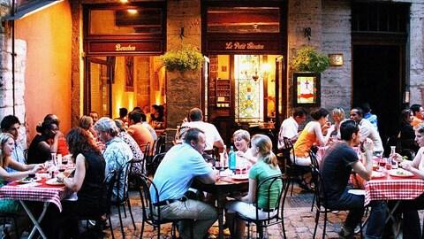 Des gens qui mangent sur une terrasse.