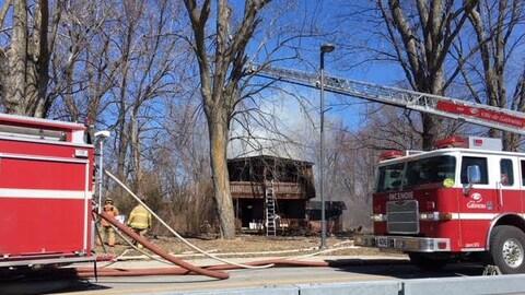 Des camions de pompier devant une résidence en feu.