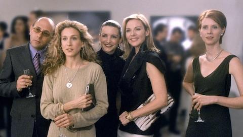 Quatre femmes et un homme regardent droit devant eux, à la fois surpris et amusés lors d'un événement mondain.