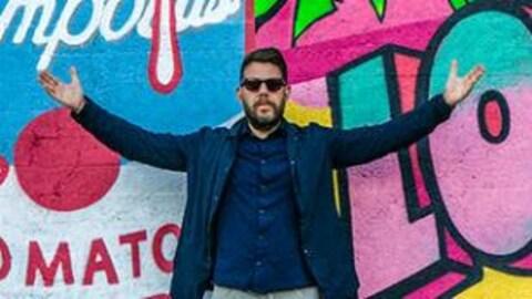 Photo de l'illustrateur, muraliste, ''pop artist'' Tava posant devant l'une de ses murales dans la rue.
