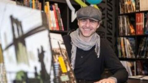 L'auteur de bande dessinée Mikaël photographié aux côtés des Tome 1 et 2 de sa série Giant.