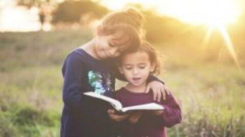 Deux petites filles debout et côte-à-côte dans  un pré ensoleillé tiennent un livre qu'elles lisent à deux.