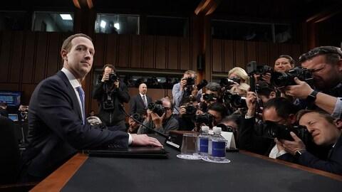 Une photo montrant Mark Zuckerberg assis à un bureau devant de très nombreux photographes.
