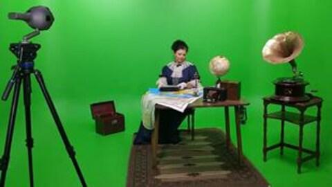 Une femme en costume d'époque est assise à son bureau devant un écran vert.