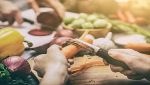 Une main qui épluche une carotte sur une table remplie d'autres légumes.