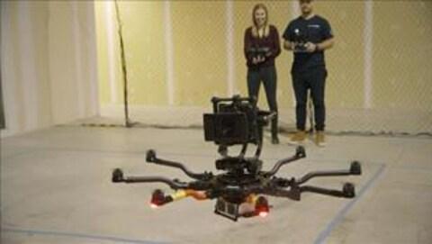 Un homme et une femme manipulent un drone.