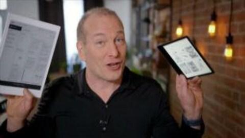 Le chroniqueur Pascal Forget tient dans sa main droite un document en papier et dans sa main gauche une liseuse.