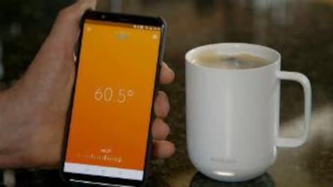 Photographie du téléphone intelligent dans la main du chroniqueur placé à côté d'une tasse de café. Sur l'écran du téléphone, devenu orange, une température s'affiche: 62,5 degrés.