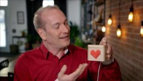 Pascal Forget nous montre un cube de bois illustré d'un coeur.