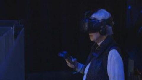 La grand-mère de notre journaliste Geneviève Tardif en pleine expérience de réalité virtuelle, casque sur la tête et manette à la main dans une pièce obscure.