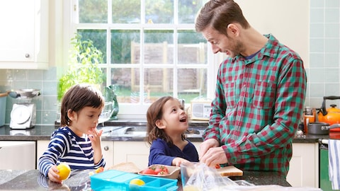 Un père prépare les boites à lunch de ses enfants.