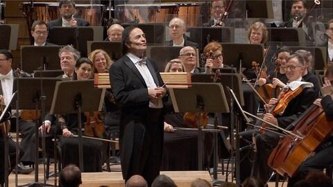 Charles Dutoit est debout sur scène, au milieu d'un orchestre.