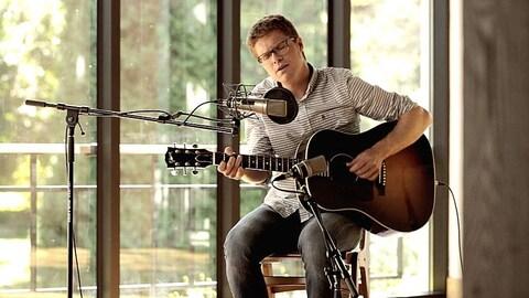 Vincent Vallieres joue de la guitare, assis sur un banc, devant un micro d'enregistrement