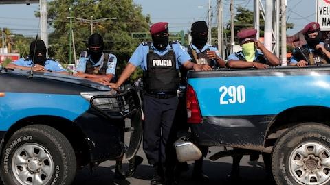 Six policiers encagoulés et alignés bloquent le passage avec leurs véhicules.
