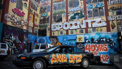 L'édifice 5Pointz en octobre 2013, recouvert de graffitis. On y voit notamment un hélicoptère, une ampoule ou encore un homme regardant vers le bas.