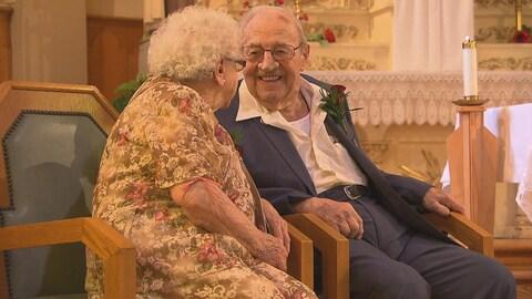 Une femme âgée, assise dans une église, se tourne vers son conjoint qui lui sourit.