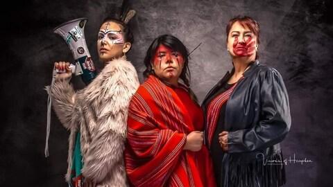 Trois femmes en habits traditionnels et portant du maquillage posent pour l'oeuvre. L'une d'entre elles tient en main un porte-voix.