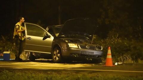 Une voiture accidentée et un policier qui l'observe.