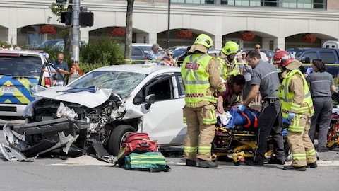 Photo de la scène d'accident : on aperçoit la voiture de l'accusé, des pompiers et des ambulanciers.