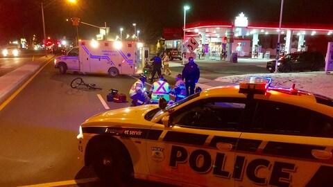 Les premiers secours au chevet d'une cycliste ainsi qu'une ambulance et une voiture de police.