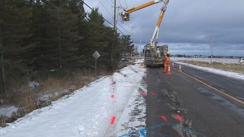 Des lignes rouges sur la chaussée se rendent jusqu'à un poteau de téléphone, près d'un camion d'Hydro-Québec.