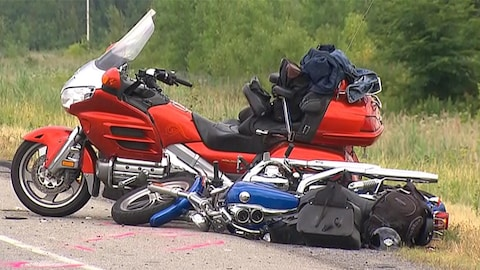 Une moto renversée sur le sol.