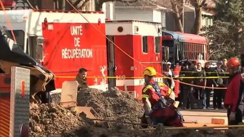 Des pompiers s'affairent dans le chantier sous le regard des badauds.