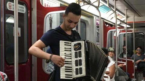 Photo d'un jeune homme qui joue de l'accordéon à bord d'une rame de métro