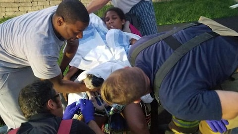 Des ambulanciers paramédicaux prêtent mains forte à la femme. Elle est en détresse.
