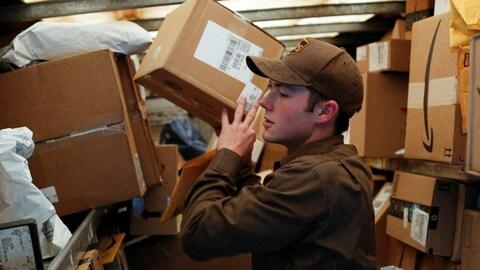 Photo d'un livreur de la compagnie UPS habillé en brun en train de soulever une boîte.